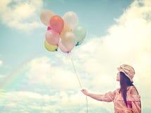 拿着五颜六色的气球和飞行在云彩天空背景的愉快的年轻红色头发妇女 库存照片