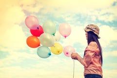 拿着五颜六色的气球和飞行在云彩天空背景的愉快的年轻红色头发妇女 免版税图库摄影