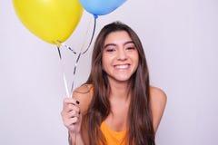拿着五颜六色的气球的愉快的少妇 免版税图库摄影