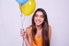 拿着五颜六色的气球的愉快的少妇 库存照片