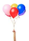 拿着五颜六色的气球的手 库存图片