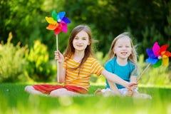 拿着五颜六色的玩具轮转焰火的两个逗人喜爱的小女孩在温暖和夏日 库存照片