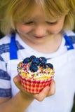 拿着五颜六色的自创杯形蛋糕的逗人喜爱的孩子 图库摄影
