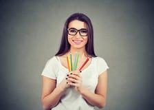拿着五颜六色的蜡笔铅笔的快乐的激动的年轻女人 免版税图库摄影