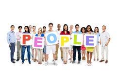 拿着五颜六色的词人民的不同的人民 库存照片