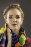拿着五颜六色的围巾的美丽的妇女画象对她的面孔 库存照片