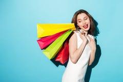 拿着五颜六色的购物袋的一个愉快的女孩的画象 库存图片