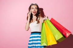 拿着五颜六色的购物袋的一名年轻微笑的妇女的画象 免版税库存照片