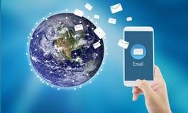 拿着人检查和传送与电子邮件的手信息在世界背景的一个电话 图库摄影