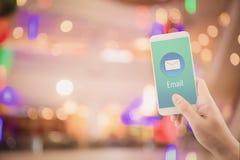 拿着人检查和传送与电子邮件的手信息在抽象bokeh背景的一个电话 免版税图库摄影