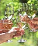 拿着人白葡萄酒的玻璃 库存照片