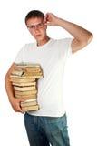 拿着人spactacles的书堆积年轻人 免版税库存图片