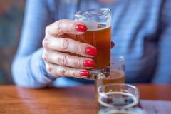 拿着从啤酒飞行的妇女宏观特写镜头一块玻璃 免版税库存照片