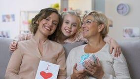 拿着从女孩的妈妈和老婆婆礼物,摆在照相机,母亲节 股票视频