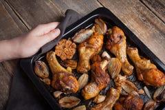 拿着从烤箱的女性手热的烤板烘烤了鸡腿用青葱和大蒜 妇女投入一张黑暗的木桌w 免版税库存图片