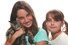 拿着他们的幼小小猫的二个姐妹 免版税库存照片