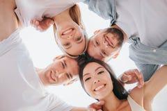 拿着他们的接近彼此的头和看下来在照相机的正面十几岁的好的图片 他们微笑着 免版税库存照片