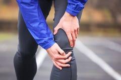 拿着他受伤的膝盖的一个年轻赛跑者的播种的射击,当ru时 库存图片