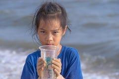 拿着他在环境干净的概念的海滩发现的塑料杯子的孩子 库存照片