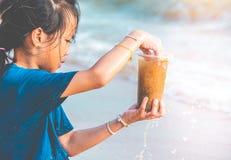 拿着他在环境干净的概念的海滩发现的塑料瓶的孩子 免版税库存照片