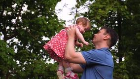 拿着他她的胳膊的愉快的爸爸心爱的女儿亲吻她在面颊和微笑 股票视频