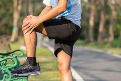 拿着他的体育腿部受伤的年轻健身人 肌肉痛苦在训练期间 有亚洲的赛跑者膝盖疼痛和问题以后 免版税库存图片