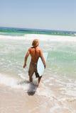 拿着他的冲浪板的新白肤金发的人 库存图片