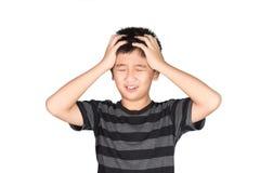 拿着他的头的亚洲男孩孩子皱眉与尖叫 拉 免版税图库摄影