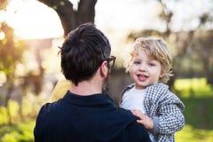 拿着他的小孩儿子外面春天自然的父亲 免版税库存照片