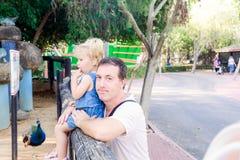 拿着他的小孩女儿的父亲画象看对自然在动物园公园 家庭休息,一起花费时间概念 免版税库存照片