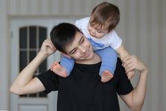 拿着他的弟弟的愉快的微笑的少年男孩坐他的脖子 免版税库存图片