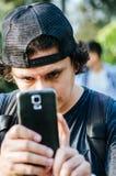 拿着他的智能手机用他的手的一个可爱的青少年的男孩的画象和拍摄照片 免版税库存图片