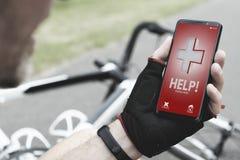 拿着他的智能手机的受伤的骑自行车的人告诉救援队 免版税库存图片