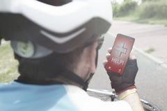 拿着他的智能手机的受伤的骑自行车的人告诉救援队 免版税图库摄影