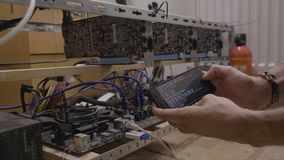 拿着他的智能手机的贸易商人在与隐藏开采的软件程序跑的gpu cryptocurrency开采的船具附近 股票录像