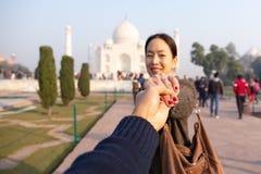 拿着他的有泰姬陵的人妻子手陈列结婚戒指在背景中 免版税库存图片