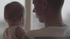 拿着他的胳膊的后面观点的人一点女婴在窗口特写镜头前面 父权喜悦  ? 股票视频