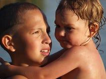 拿着他的胳膊的少年男孩的画象一个妹妹反对天空蔚蓝 免版税库存照片