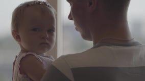 拿着他的胳膊的帅哥一点女婴在窗口特写镜头前面 父权喜悦  爱的家庭在 影视素材