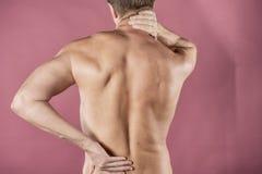 拿着他的脖子和腰部在痛苦中的人,隔绝在桃红色背景 医疗保健和医学 遭受背部疼痛 免版税库存照片