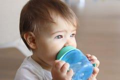 拿着他的蓝色瓶和饮用水的逗人喜爱的矮小的婴孩 库存图片
