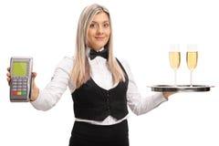 拿着付款终端和一个盘子有两块玻璃的女服务员 库存照片