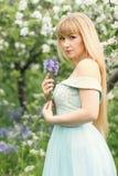 拿着会开蓝色钟形花的草的诗句妇女 库存照片