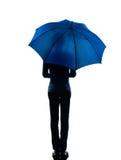 拿着伞剪影的妇女背面图 免版税库存照片
