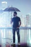 拿着伞的丝氨酸人在抽象大都会 免版税库存图片
