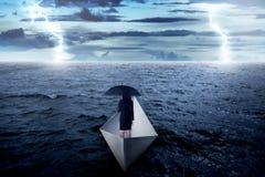 拿着伞的亚裔女商人单独在海,航行与纸小船 免版税库存照片
