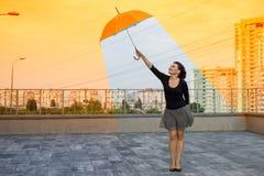 拿着伞的全球性变暖妇女是在舒适的cli 库存照片