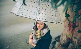 拿着伞的女孩在一个秋天雨天 免版税库存照片