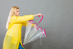 拿着伞的妇女佩带的雨衣 免版税库存图片