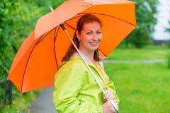 拿着伞的微笑的女孩在雨下 库存照片